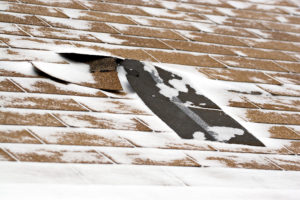 Damaged roof shingles blown off during a windy winter storm.